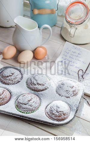 Decorating Delicious Muffins With Caster Sugar On Old White Table