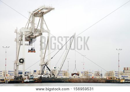 Oakland CA - November 15 2016: Tugboat PHILLIS T securing a barge ship against the docks at the Port of Oakland while crews work on dredging the to keep waterways navigable.