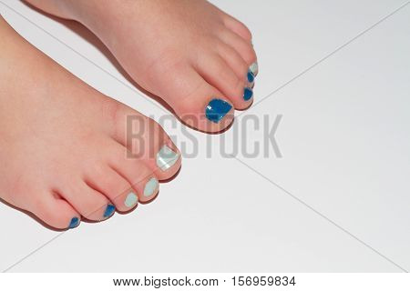 Young boys feet with painted toe nails on white background.