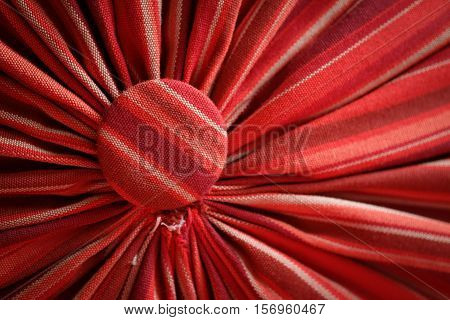 Pleated fabric red with head studs close up abstract background texture