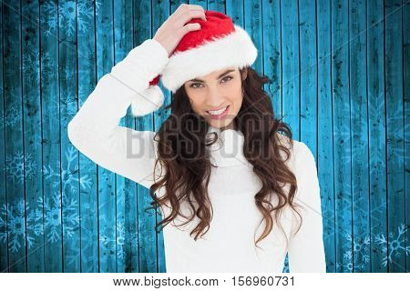 Beautiful woman in santa hat smiling at camera during christmas time
