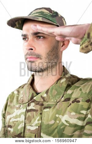 Close-up of confident soldier saluting against white background