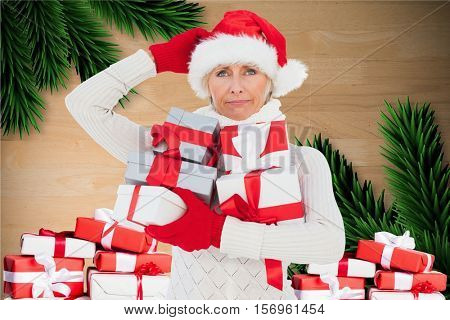 Confused woman in santa hat holding christmas gift against digitally generated background