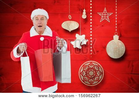 Portrait of man in santa costume holding shopping bags against digitally generated background during christmas time