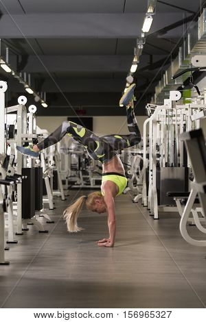 Woman Standing On Hands In Fitness Center