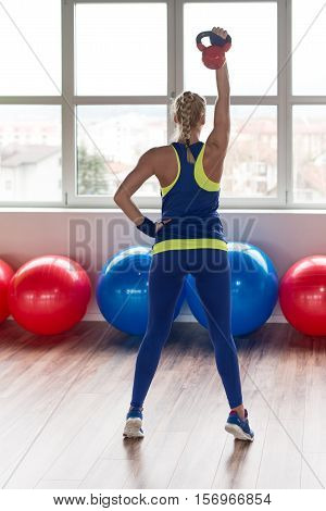 Fitness Woman Using Kettlebells Inside Gym