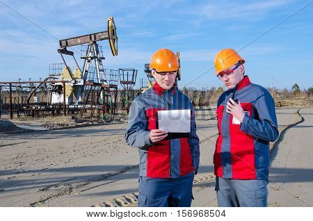 Workers in the oilfield one talking on the radio. Pump jack and wellhead background. Oil and gas concept.
