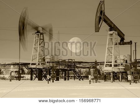 Working oil pump jack at night time. Full moon. Oilfield during winter. Oil and gas concept. Toned.