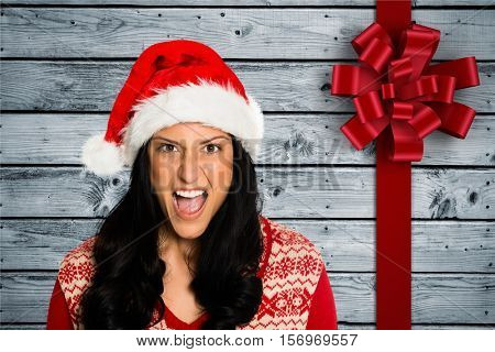 Portrait of excited woman in santa hat standing against wooden background with red ribbon