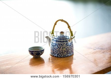 Teapot and cups on table in the sunrise