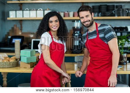 Portrait of smiling waiter and waitress leaning at counter in cafe