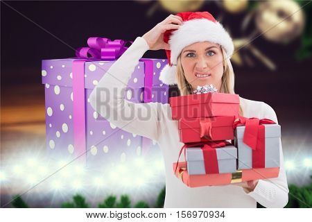 Confused woman holding stack of christmas gifts against digitally generated background