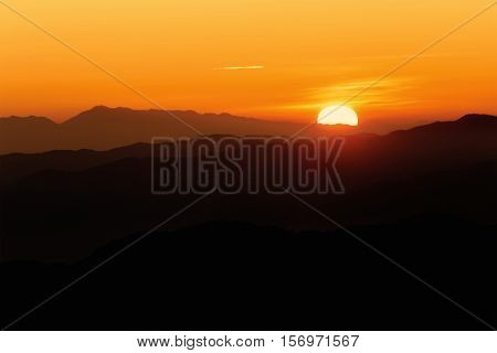 Brilliant and colorful orange sunset with silhouette of mountain range