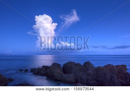 Tall white thunderhead cloud formation casts reflection over calm Caribbean Sea at Punta Soldado on Isla Culebra on a clear dusk evening