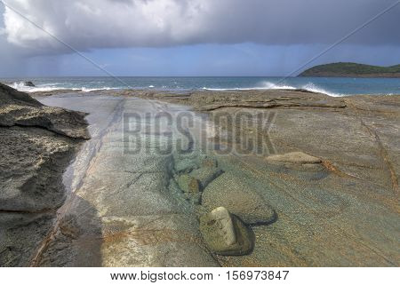 Shallow tide pool on rocky northeast shore of Isla Culebra at lowtide as gray clouds drop rain over the sea