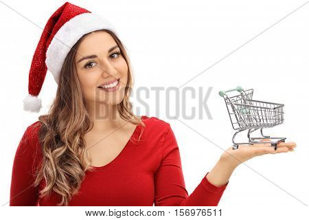 Happy young woman with a Christmas hat holding a small empty shopping cart isolated on white background