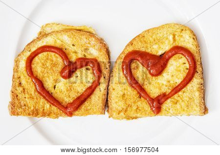 Two fried breads in the egg with hearts of ketchup on white plate. Valentine theme. Creative food. Positive emotions.