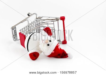 Santa Claus dropped out from the shopping cart. A conceptual representation of wrong gift or forgotten. Of rampant consumerism and the loss of the true spirit of Christmas.