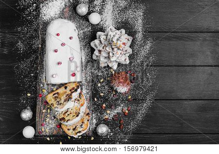 Christmas stollen. Traditional German European festive dessert. Ingredients cranberries pine nuts for Christmas Stollen. Stollen cake cut into pieces. Christmas food card. Black background. Top view. blank space