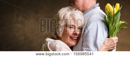 Older Smiling Woman Holds Tulips