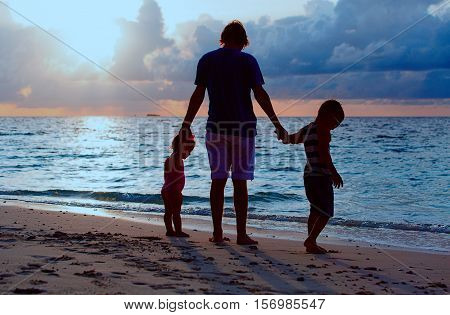 father and two kids walking at sunset beach