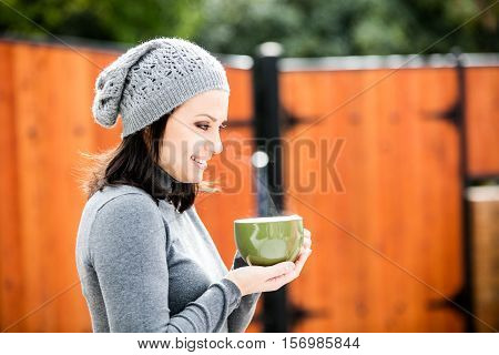 Beautiful young woman in warm clothes and gray hat smiling, drinking tea in a big cup outdoors in autumn time
