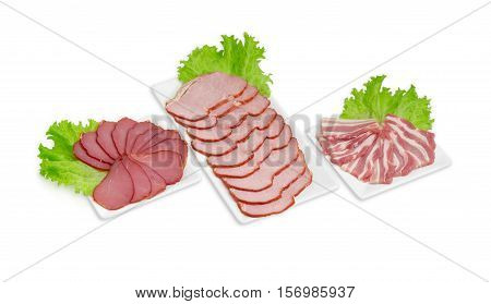 Sliced cured pork tenderloin smoked pork loin and bacon on a lettuce leaves on the three rectangular white dishes on a light background