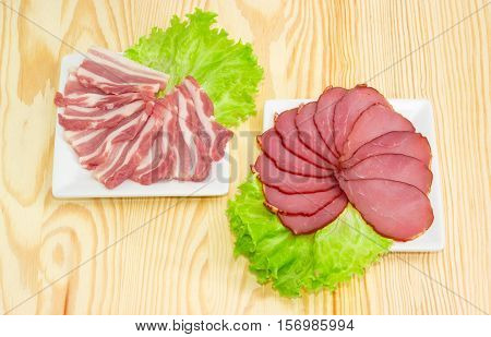Sliced bacon and cured pork tenderloin with lettuce on a square white dishes on a light wooden surface