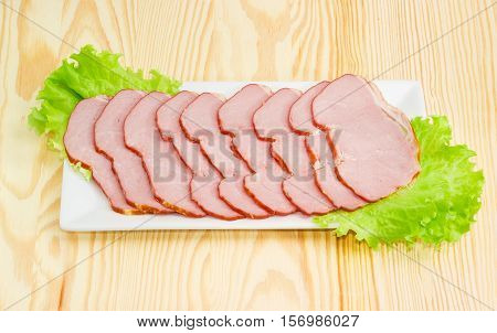 Sliced smoked pork loin on a lettuce leaves on a rectangular white dish on a light wooden surface