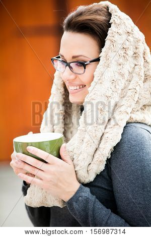 Beautiful green eyed young woman in warm clothes and beige scarf wearing vision glasses and holding a cup of tea