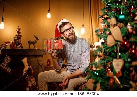Young Man in Santa Hat Sitting and Shaking Present with Interest in Cozy Room Decorated for Christmas.