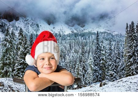 The concept of ecotourism. Very handsome boy in a red cap of Santa Claus smiling on the background of evergreen forest in the snow