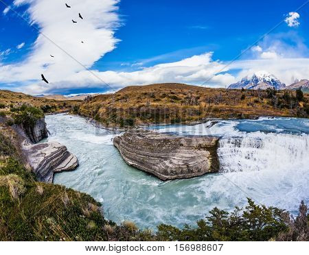 Cold water is emerald Paine river forms a cascading waterfalls. Chile, Paine Cascades. National Park Torres del Paine - Biosphere Reserve