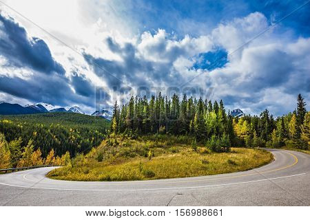 The dramatic storm clouds over the Rocky Mountains. The road bends sharply in the woods. The concept of active tourism