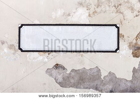 White painted area on wall, empty signboard for text