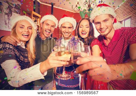 Portrait of friends wearing Christmas hats toasting against flying colours