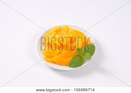 plate of peeled and sliced peaches on white background