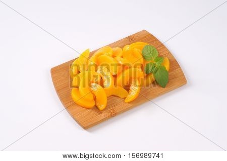 pile of peeled and sliced peaches on wooden cutting board