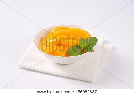 bowl of peeled and sliced peaches on white place mat