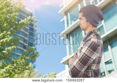 Side view of confident hipster with arms crossed against view of buildings