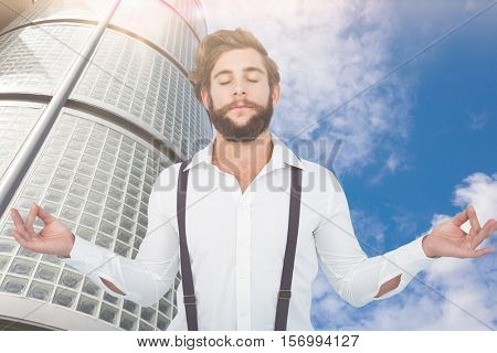Hipster meditating arms outstretched against low angle view of skyscraper