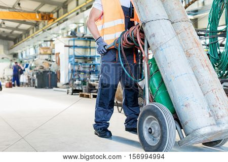 Low section of young manual worker moving gas cylinders in metal industry
