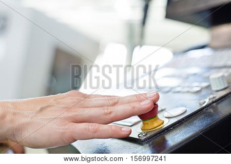 Close-up of manual worker pressing button on industrial control panel at factory