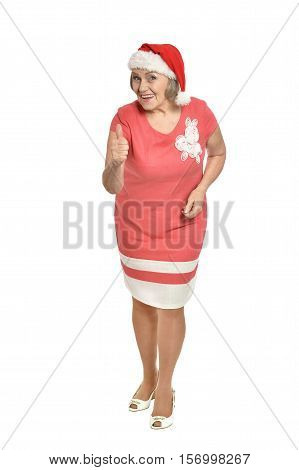 Full lenght portrait of happy  senior woman in Santa hat showing thumb up isolated on white background