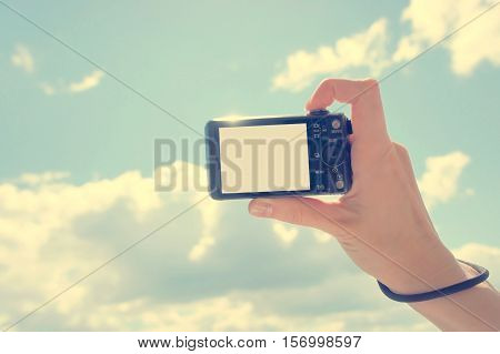Hand holding digital camera. Girl's hand with the camera against the sky. Empty space for your picture or text.