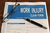 insurance: blank work injury claim form on desk poster