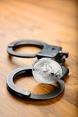 Silver Bitcoin coins and handcuffs on wooden table. Law problems or arrest concept poster