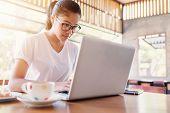 Business entrepreneur asian girl working online on laptop in cafe. business entrepreneur asian using laptop in home. poster
