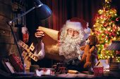 Merry Christmas and Happy Holidays! Santa Clause is preparing gifts for children for Xmas at his desk at home. Christmas legends and traditions. poster