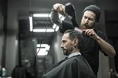 Unbelievable barber with a beard and a tattoo is drying the hair of his client in a black cutting hair cape in the barbershop. He is using a black hairdryer and a hairbrush. Horizontal. poster